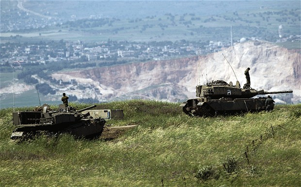 Israeli soldiers stand on top of tanks in the Golan Heights, Israel, near the Syrian town of Kan Arnaby