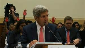 Kerry wants war; protesters with red hands do not.